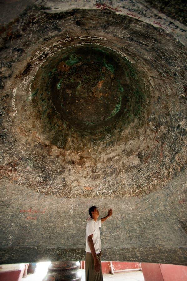 Man under a Mingun bell in Myanmar. Man inside under Mingun Bell is the largest ringing Bell in the World,located at Mingun temple,Sagaint Region in Myanmar stock images