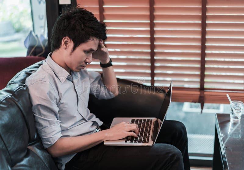 Man under mycket spänning genom att använda bärbar datordatoren i kafé royaltyfria foton