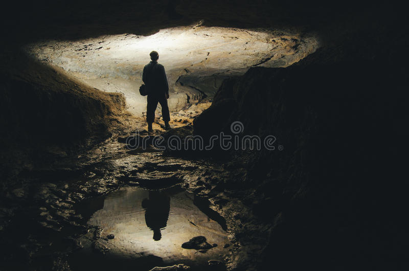 Man in underground dark cave. Silhouette of man exploring in underground dark cave royalty free stock images