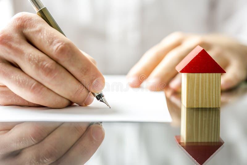 Man underteckning av ett avtal, när du köper ett nytt hus royaltyfri foto