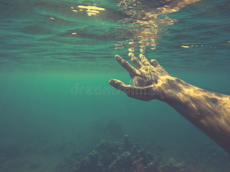 Man underwater hand reaching for sunlight. royalty free stock images