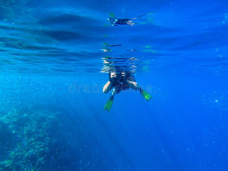Man with underwater photocamera in blue sea water. Snorkeling in tropical seaside. Summer vacation in exotic island stock images