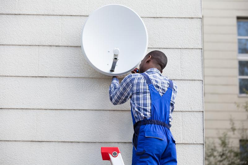 Man In Uniform Fitting TV Satellite Dish. Young African Man In Uniform Fitting TV Satellite Dish On Wall stock images