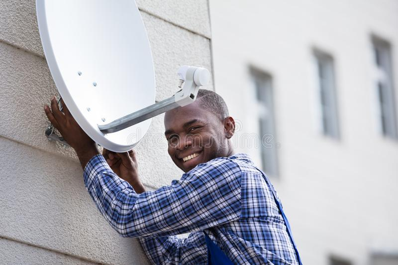 Man In Uniform Fitting TV Satellite Dish. Young African Man In Uniform Fitting TV Satellite Dish On Wall royalty free stock photo