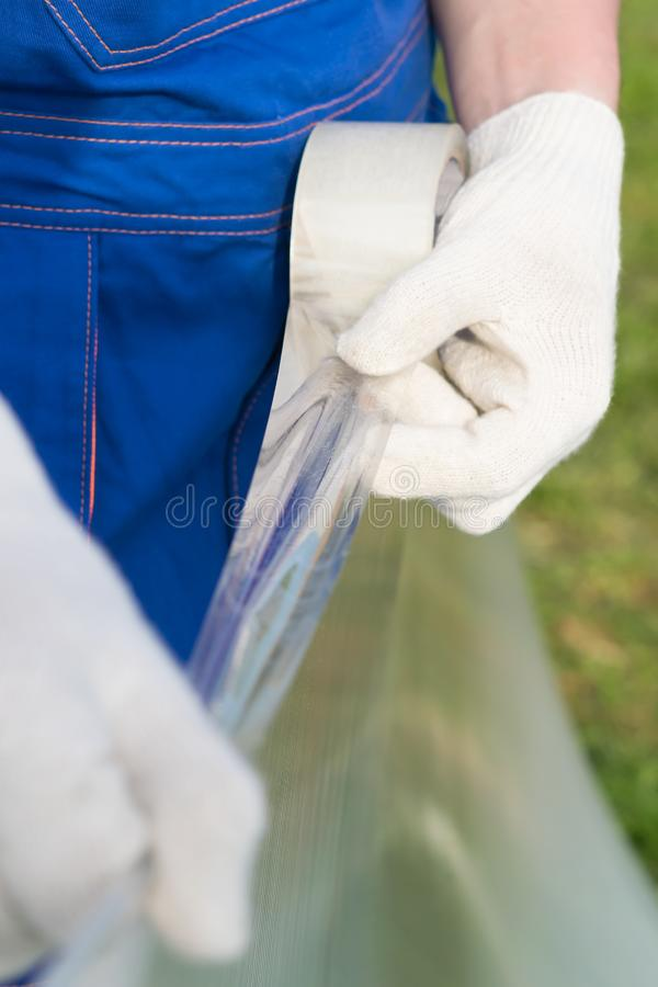 Man in uniform glues adhesive tape to polycarbonate close up royalty free stock image