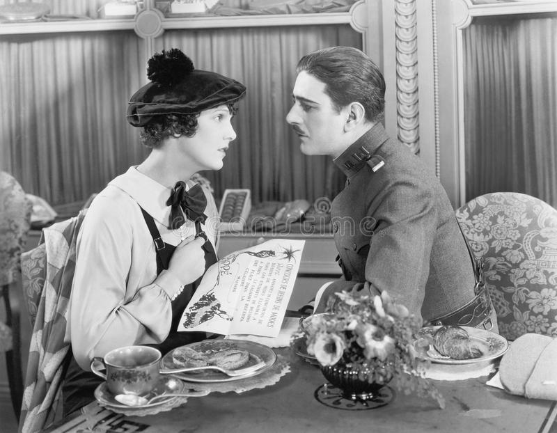 Man in uniform and a woman sitting together at a table and looking at each other. (All persons depicted are no longer living and no estate exists. Supplier stock photography