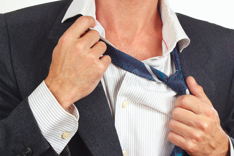 Man unleashes his tie over business suit closeup. Man unleashes his tie over business suit close up royalty free stock photo