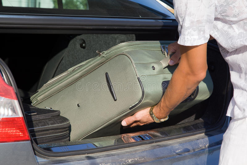 Man unload boot of a car. Closeup hand with suitcase royalty free stock images
