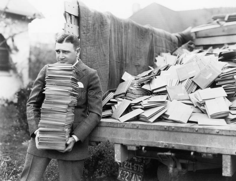 Man unloading a truck full of letters royalty free stock photos