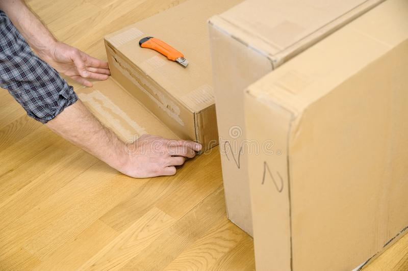 A man is unpacking the cardboard boxes. It is opening the side of the package royalty free stock photos