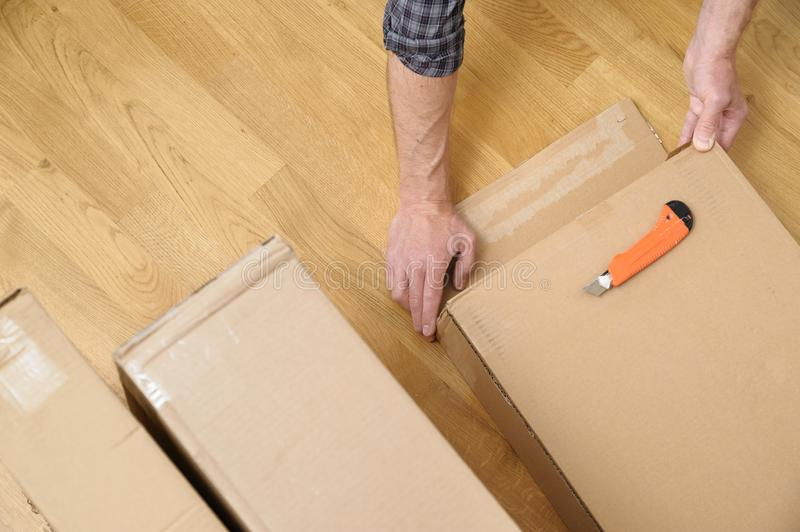 A man is unpacking the cardboard boxes. It is opening the side of the package stock image