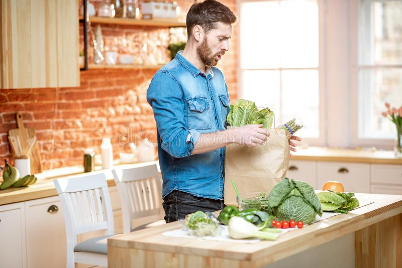 Man unpacking healthy food on the kitchen. Handsome man in blue shirt unpacking healthy food from the shopping bag on the kitchen royalty free stock photos