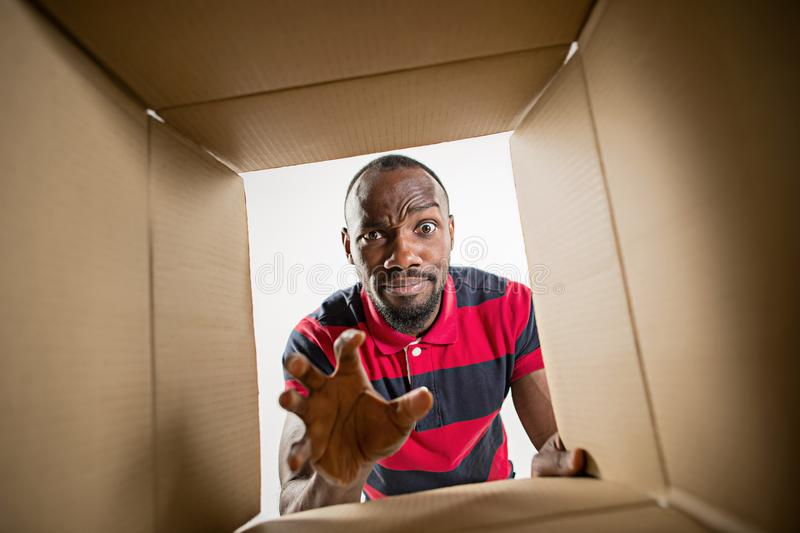Man unpacking and opening carton box and looking inside. The surprised afrocan man unpacking, opening carton box and looking inside. The package, delivery royalty free stock photos