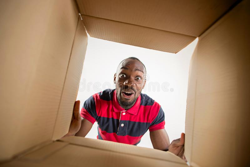 Man unpacking and opening carton box and looking inside. The surprised afrocan man unpacking, opening carton box and looking inside. The package, delivery royalty free stock images