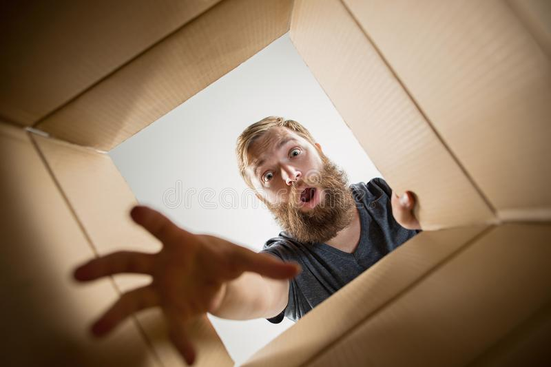 Man unpacking and opening carton box and looking inside. The surprised man unpacking, opening carton box and looking inside. The package, delivery, surprise royalty free stock images