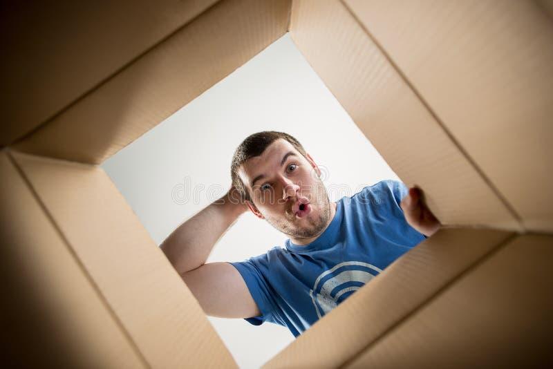 Man unpacking and opening carton box and looking inside. The surprised man unpacking, opening carton box and looking inside. The package, delivery, surprise royalty free stock photography