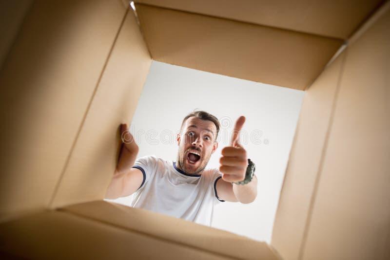 Man unpacking and opening carton box and looking inside. The surprised man unpacking, opening carton box and looking inside. The package, delivery, surprise royalty free stock image