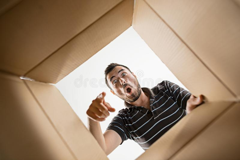 Man unpacking and opening carton box and looking inside royalty free stock images