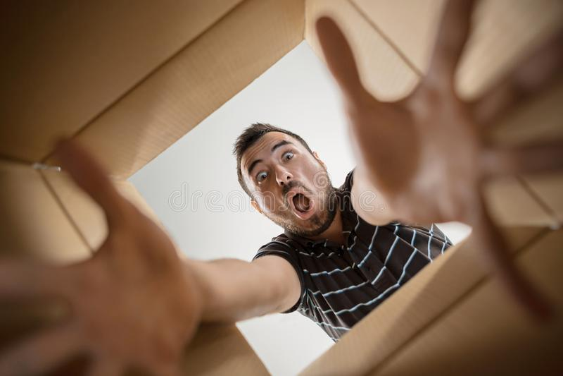Man unpacking and opening carton box and looking inside. The surprised man unpacking, opening carton box and looking inside. The package, delivery, surprise stock photography