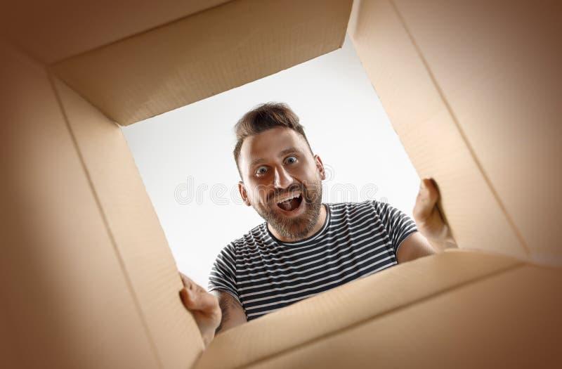 Man unpacking and opening carton box and looking inside. The surprised man unpacking, opening carton box and looking inside. The package, delivery, surprise stock photos