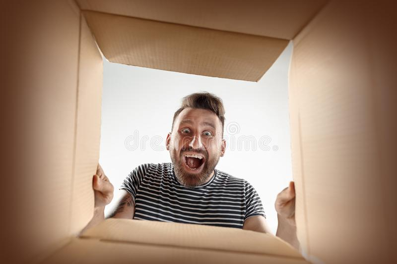 Man unpacking and opening carton box and looking inside. The surprised man unpacking, opening carton box and looking inside. The package, delivery, surprise stock images