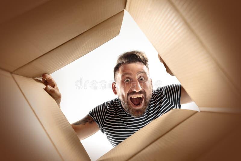 Man unpacking and opening carton box and looking inside. The surprised man unpacking, opening carton box and looking inside. The package, delivery, surprise stock image