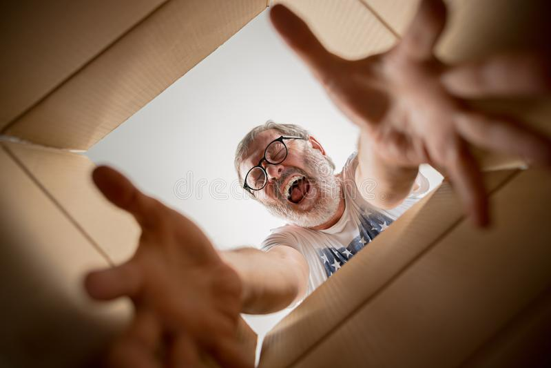 Man unpacking and opening carton box and looking inside. The surprised senior man unpacking, opening carton box and looking inside. The package, delivery royalty free stock image