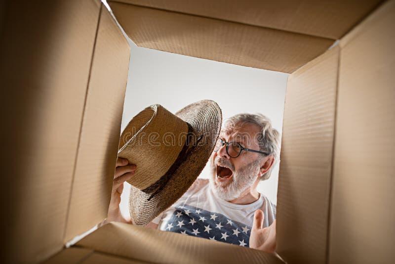 Man unpacking and opening carton box and looking inside. The surprised senior man unpacking, opening carton box and looking inside. The package, delivery stock photos