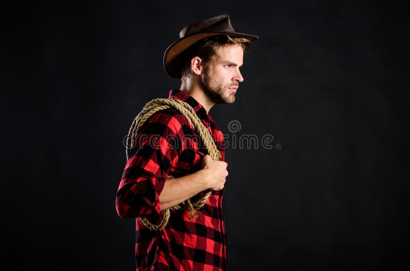 Man unshaven cowboy black background. Man wearing hat hold rope. Lasso tool of American cowboy. Lasso is used in rodeos. As part of competitive events. Lasso royalty free stock photo