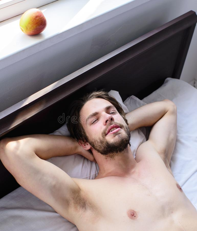 Man unshaven handsome guy naked torso relaxing bed. Guy macho lay white bedclothes. Man sleepy drowsy unshaven. Bearded face having rest. Pleasant relax concept royalty free stock images