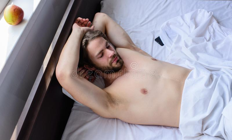 Man unshaven handsome guy naked torso relaxing bed. Let your body feel comfortable. Guy macho lay white bedclothes. Man sleepy drowsy unshaven bearded face royalty free stock photo