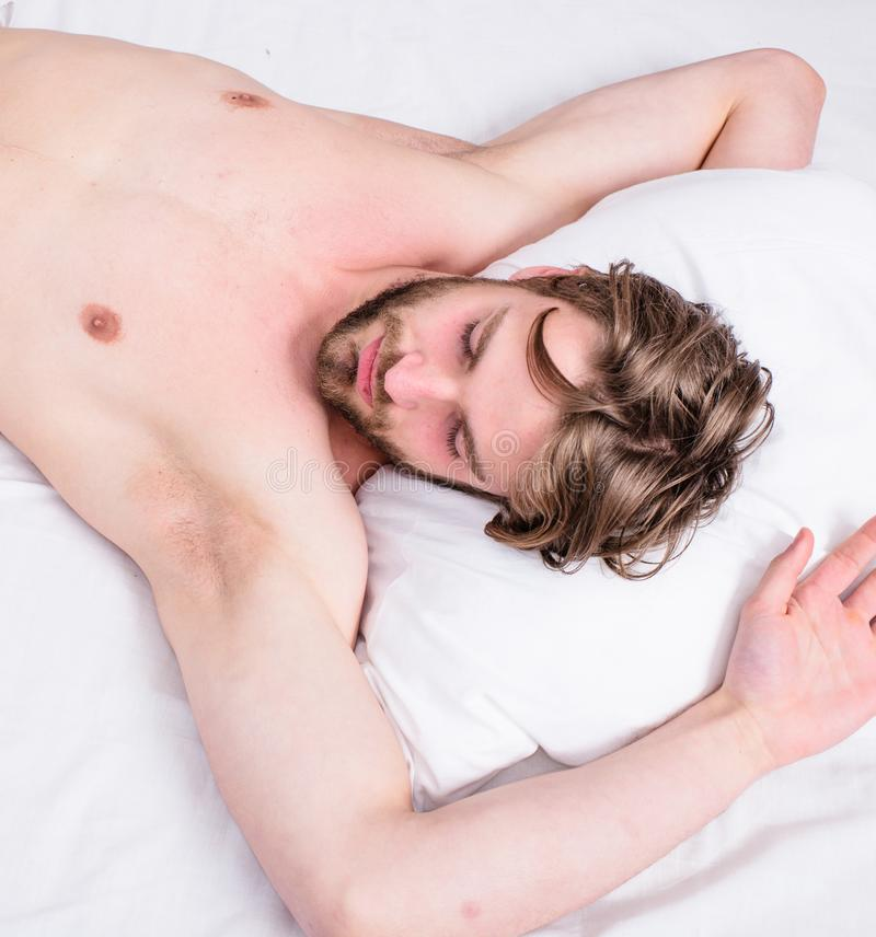 Man unshaven handsome guy naked torso relaxing bed top view. Guy macho lay white bedclothes. Man sleepy drowsy. Bearded face having rest. Pleasant awakening stock photos