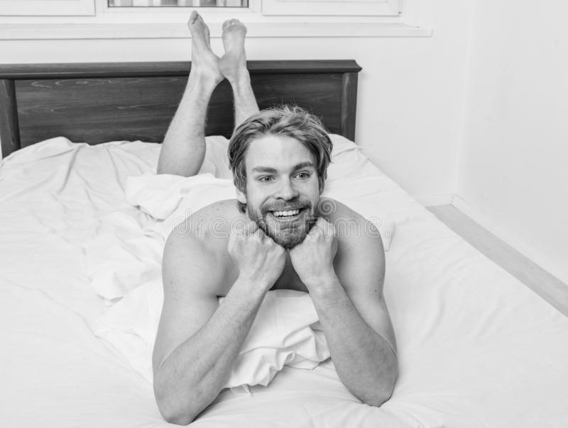 Man unshaven handsome happy smiling torso relaxing bed. Guy macho lay white bedclothes. Man feel full of energy. After pleasant night dream. Pleasant relax royalty free stock image