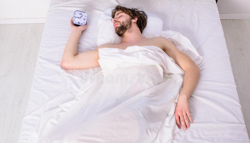 Man unshaven relaxing bed hold alarm clock. Man sleepy drowsy unshaven bearded face covered with blanket having rest stock photography