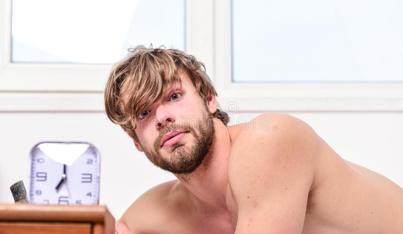 Man unshaven tousled hair wakeful face having rest. Good morning. Man unshaven lay bed near alarm clock. Stick schedule. Enough sleep for him. Morning alarm stock photography