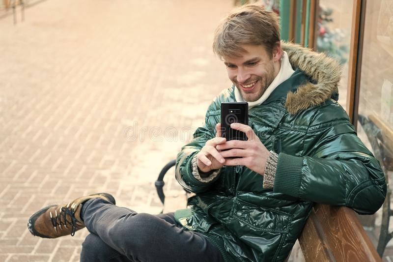 Man unshaven wear warm jacket and hold smartphone snowy urban background. Communication concept. Hipster use smartphone stock images