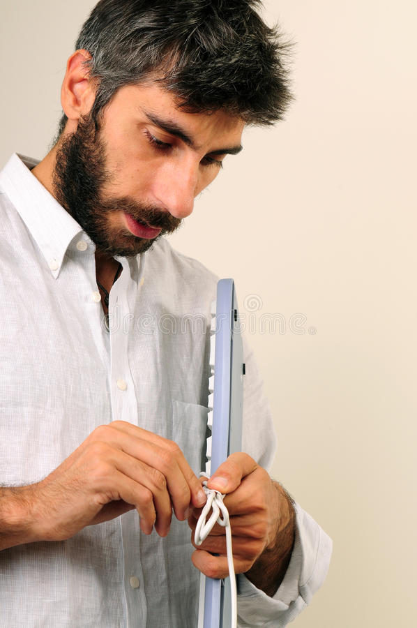 Man Untying Cable Of The Keyboard. He look confuse stock image