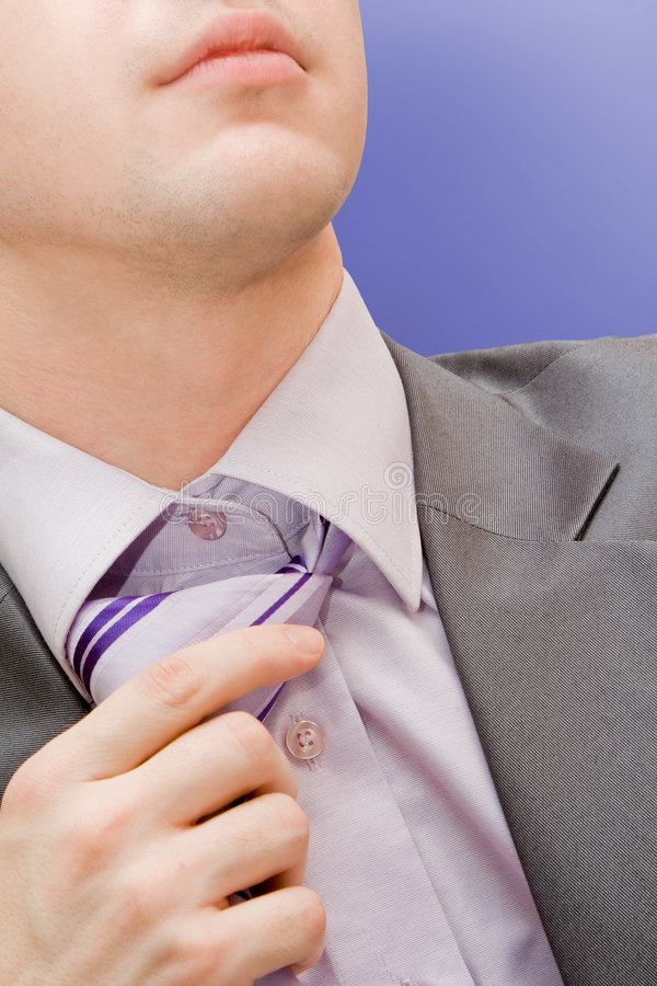 Man untying a necktie. A handsome businessman fed up with business royalty free stock photos