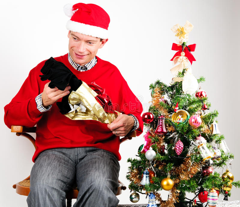 Man unwrapping a Christmas gift. Man in red sweater unwrapping a Christmas gift royalty free stock photos