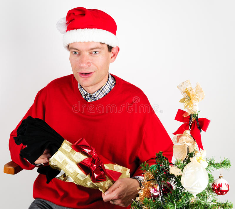 Man unwrapping a Christmas gift. Man in red sweater unwrapping a Christmas gift stock image