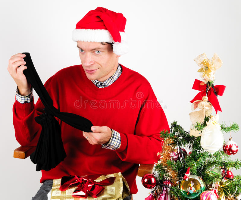 Man unwrapping a Christmas gift. Man in red sweater unwrapping a Christmas gift stock photos