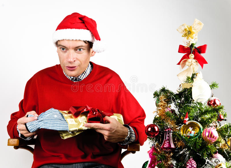 Man unwrapping a Christmas gift. Man in red sweater unwrapping a Christmas gift royalty free stock photography