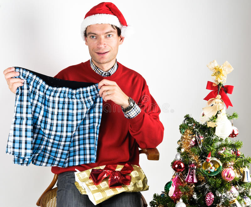 Man unwrapping a Christmas gift. Man in red sweater unwrapping a Christmas gift stock images