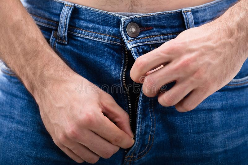 Man Unzipping The Blue Jeans royalty free stock images