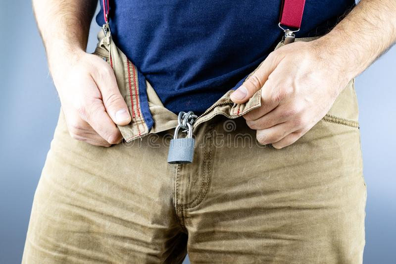 The man unzips his jeans and there is a lock on the chain mounted, yellow jeans with. A grey background royalty free stock images
