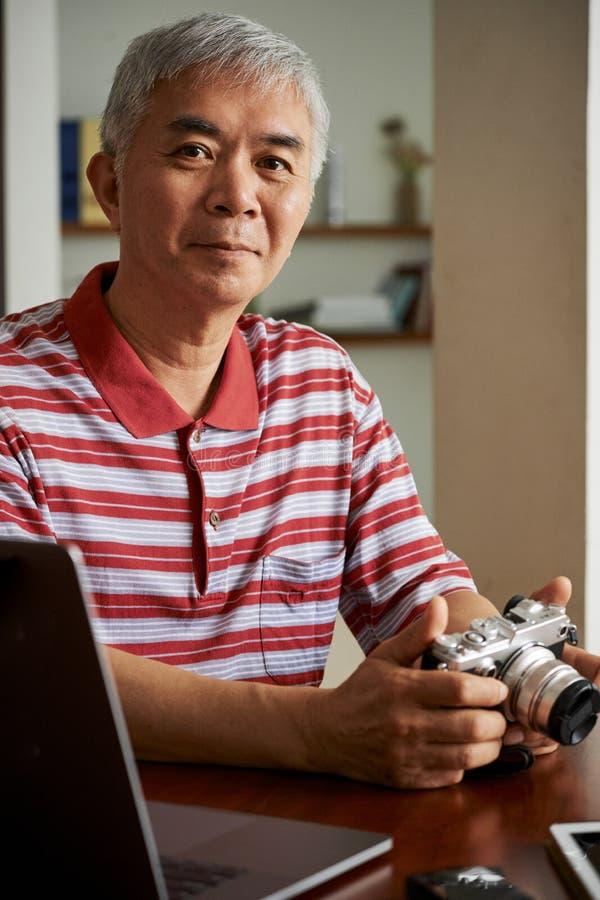 Man uploading photos from camera on laptop stock photography