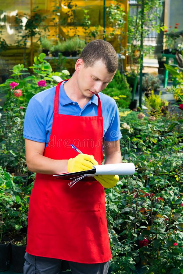 Man uppehällen ett register av växter i trädgården arkivfoton
