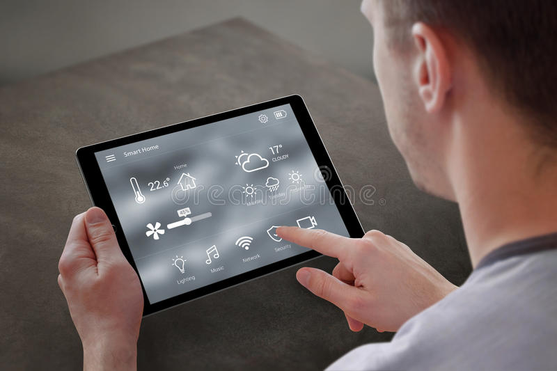 Man use application for smart home control on tablet royalty free stock images