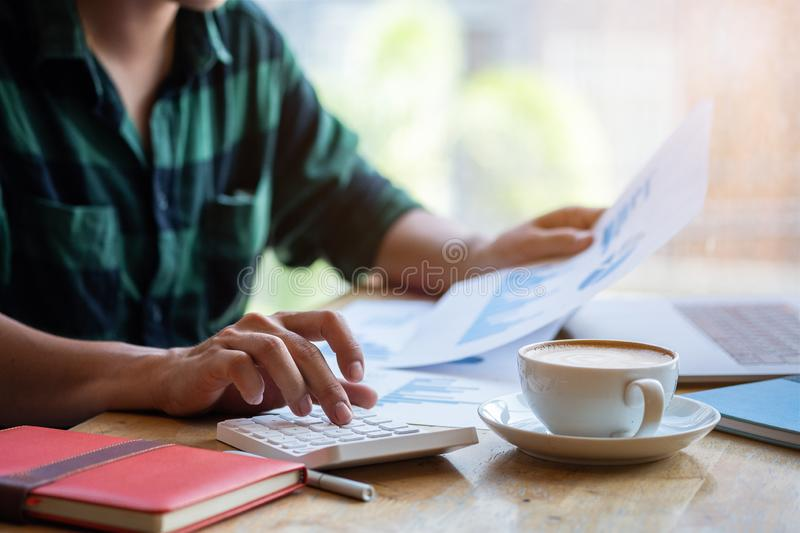 Man use calculator to calculate, Modern working life, Working in coworking space, Work in morning with coffee, Freelance concept royalty free stock photos