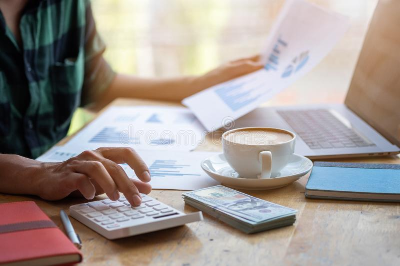 Man use calculator to calculate, Modern working life, Working in coworking space, Work in morning with coffee, Freelance concept stock photo